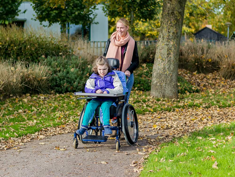 Disabled girl in a wheelchair relaxing outdoors / Disabled girl